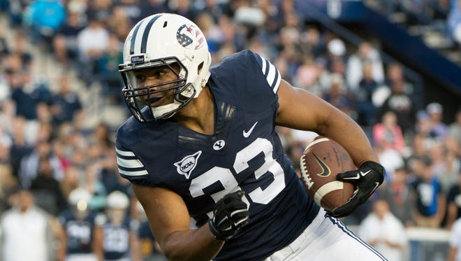 Running back Paul Lasike #33 of the BYU Cougars runs after a catching a pass against the Houston Cougars on September 11, 2014, at LaVell Edwards Stadium in Provo, Utah.