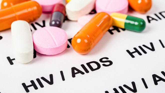 Pills on a paper that reads HIV / AIDS