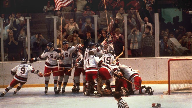 In this Feb. 22, 1980 file photo, the U.S. hockey team pounces on goalie Jim Craig after a 4-3 victory against the Soviets in the 1980 Olympics, as a flag waves from the partisan Lake Placid, N.Y. crowd.