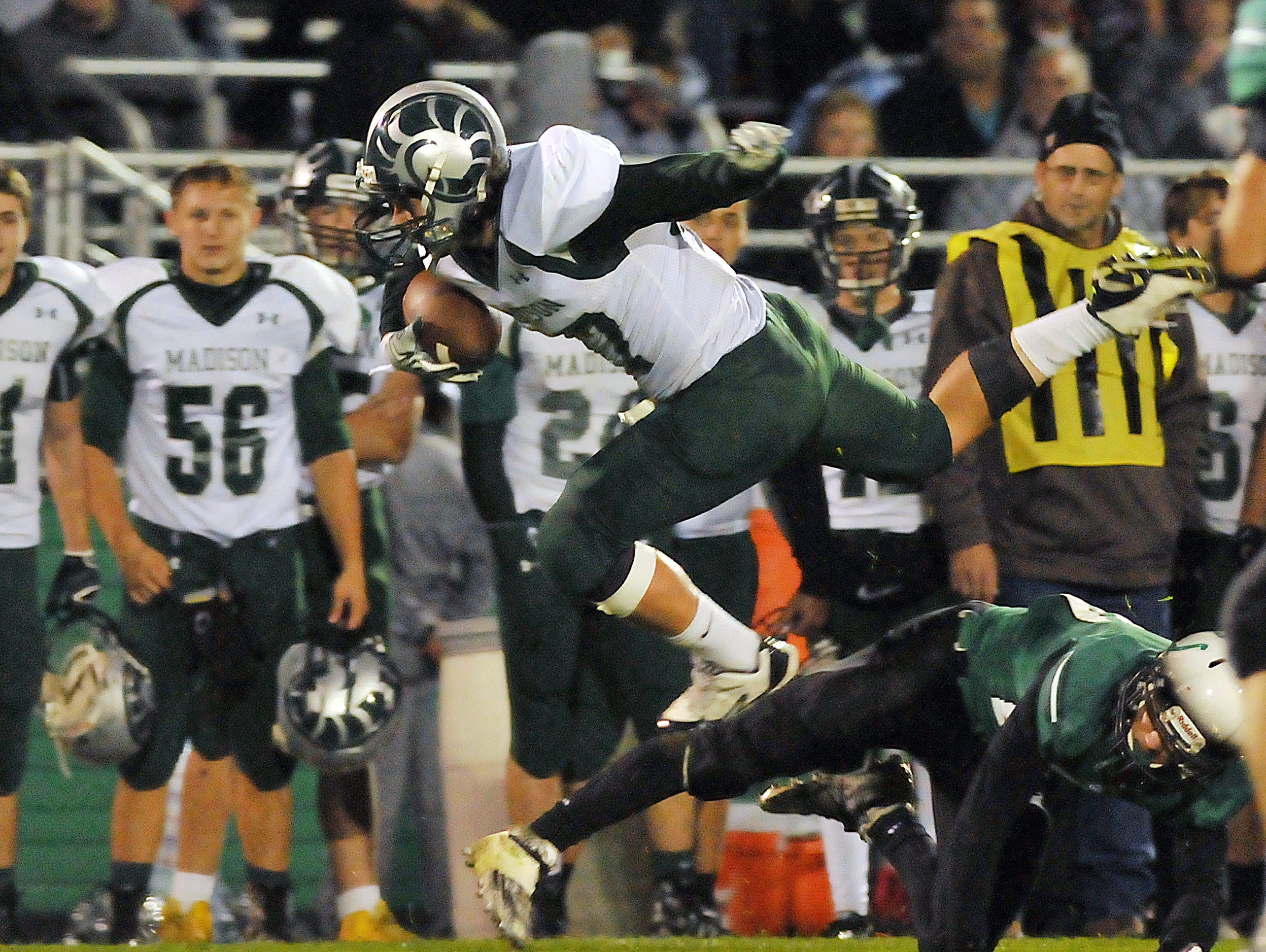 Madison's Justice Cains hurdles a Clear Fork Defender during game Friday night at Clear Fork.