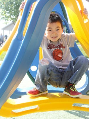 Nathan Giughlo, age 3, of Middletown, crouches as he makes his way through the obstacle course Wednesday at the new Can-Do Playground at Charles E. Price Memorial Park on Level Roads in Middletown.
