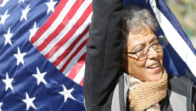 A woman holds a U.S. flag while protesting Friday at San Jacinto Plaza in Downtown El Paso. Immigrant families held a peaceful protest to mark their dedication to upholding human dignity and human rights and to protest President Donald Trumps' inauguration.
