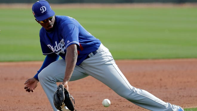 Los Angeles Dodgers second baseman Darnell Sweeney fields a ball during a spring training baseball practice, Wednesday, Feb. 22, 2017, in Phoenix. (AP Photo/Matt York)