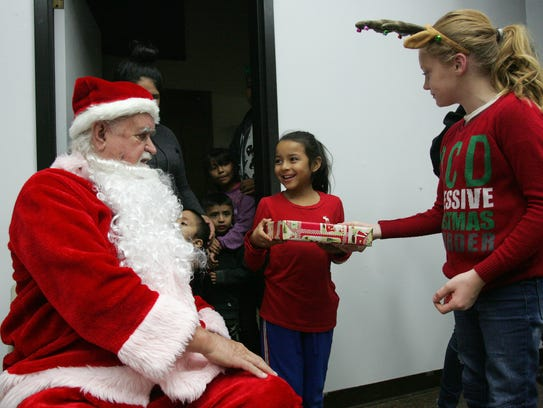 Hailey Cubias, 8, receives a present from Santa Claus