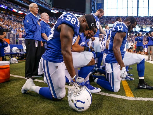 Indianapolis Colts teammates kneel together during
