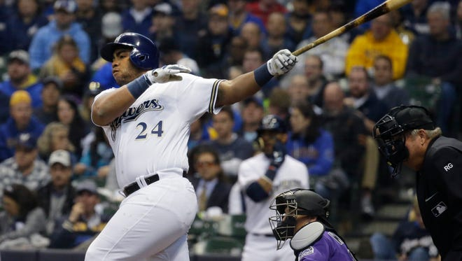 Jesus Aguilar hits a pinch-hit single in the Brewers' five-run fifth inning Monday against the Colorado Rockies on Opening Day at Miller Park.