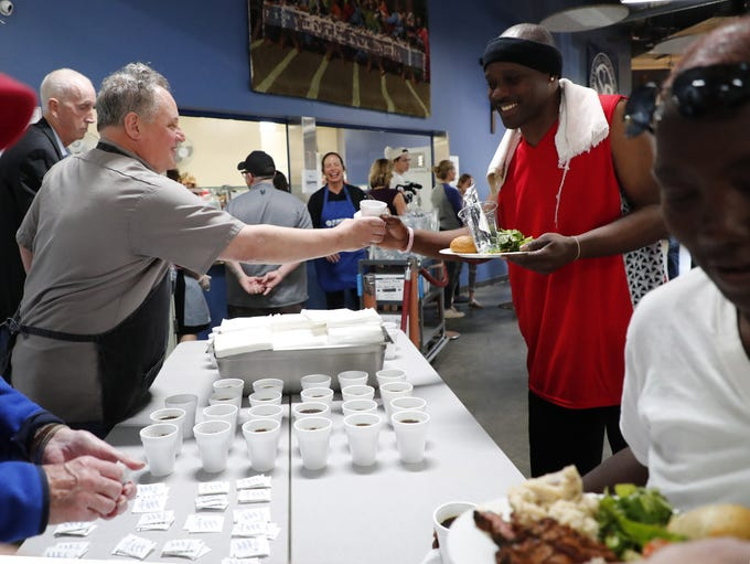 Chef Chris Bianco (left) serves drinks for the homeless