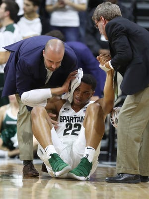 Michigan State forward Miles Bridges is tended to by team doctor Jeff Kovan after taking a spill defending Ferris State wing Jalen McFadden during the first half of MSU's 80-72 exhibition win over Ferris State on Thursday, Oct. 26, 2017, at Breslin Center.