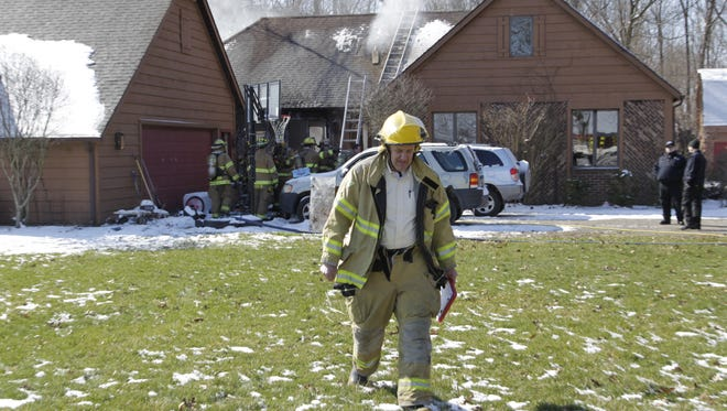 Fire fighter Steve Baker assists in the investigation of a house fire Wednesday, March 15, 2017, in the 7400 block of Goldsberry Road.