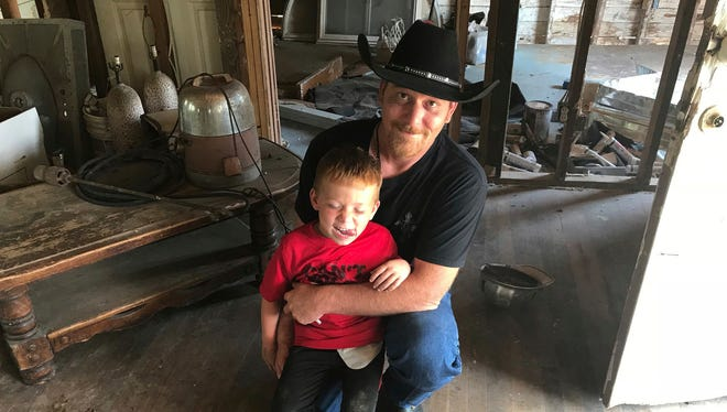 Chris Ward poses with his son, 6-year-old Ryland Ward, at the family home he and his brother are remodeling in La Vernia, Texas, on April 2, 2018. Ward lost his wife and two daughters in the shooting at the First Baptist Church of Sutherland Springs. Ryland, who was shot four times in the massacre, has undergone several surgeries and hours of physical therapy.