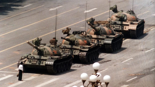 A Chinese protester blocks a line of tanks heading east on Beijing's Cangan Boulevard. on June 5, 1989, in front of the Beijing Hotel. The man, calling for an end to the violence and bloodshed against pro-democracy demonstrators, was pulled away by bystanders, and the tanks continued on their way.