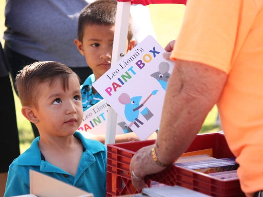 Richard Bejarano, 3, receives a free book from the Children's Reading Foundation at a recent community event.