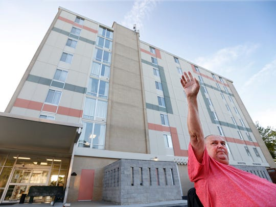 Martin Gotthardt waves to drivers as they pass by South Avenue Tower.