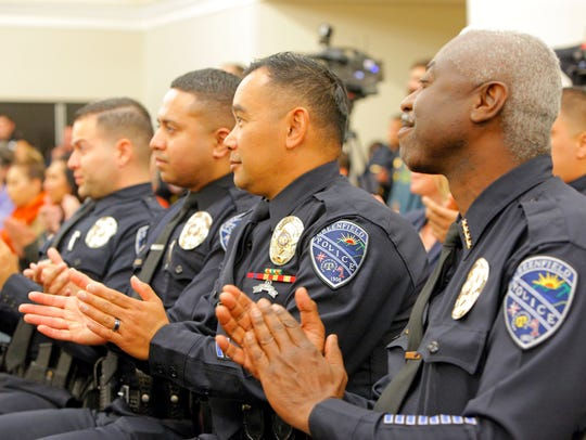 Greenfield police officers applaud during the swearing
