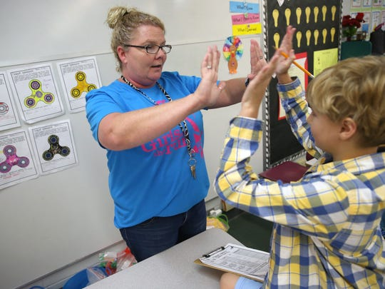 Teacher Amy Garay high-fives her student Ashton Laczko in her 3rd grade class during a STEM research experiment with Fidgets at Canopy Oaks Elementary School on Tuesday, May 16, 2017.
