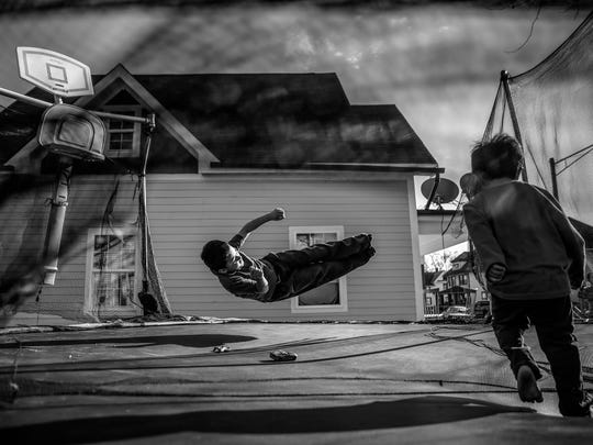 Juan Carlos Arreola, 8, and brother Alex, 3, jump on their trampoline on a sunny, yet breezy, afternoon in the Near West neighborhood on Wednesday, March 8, 2017.