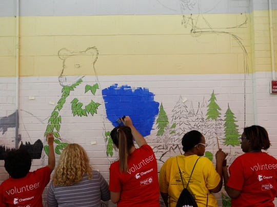 Volunteers paint S.T.E.M inspired murals on the walls on Jones Elementary school as apart of a Dr. Martin Luther King Jr. Day of Service project Monday afternoon. Multiple murals across the school will be a surprise for the children when they enter the school Tuesday.