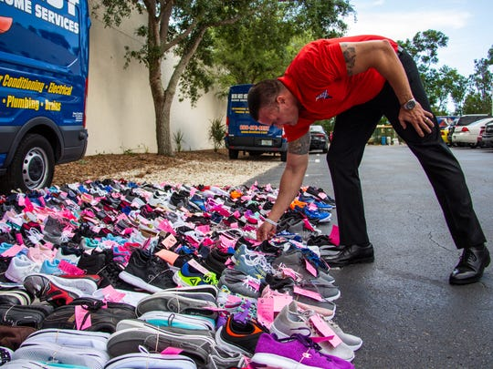 Best Home Services co-owner Keegan Hodges arranges donated shoes outside their store in Naples on Monday, June 11, 2018, which were collected from a recent shoe drive for Laces of Love.