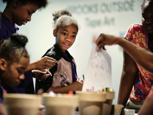 "Jazzlyn Davis (center) works on a drawing for a National Arts and Education Week activity in the rotunda of the Memphis Brooks Museum of Art during a ""pay what you can Wednesday"" at the museum. Leaders of the Memphis Brooks Museum of Art announced this week that they are considering a move from the museum's 101-year-old location in Overton Park."