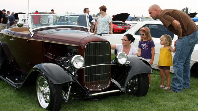 Shellie Casper, and Kiaya, Alexis and Mike Haines, look at a 1932 Ford during the 2009 Windsor Cruise In at Eastman Park.