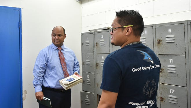 Guam Department of Education Superintendent Jon Fernandez, left, holds a worn English book during a walk-through inspection at F.B. Leon Guerrero Middle School in Yigo on June 6.
