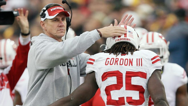 Wisconsin running back Melvin Gordon (25) celebrates with head coach Gary Andersen, left, after scoring on a 6-yard touchdown run during the first half of an NCAA college football game against Iowa, Saturday, Nov. 22, 2014, in Iowa City, Iowa.