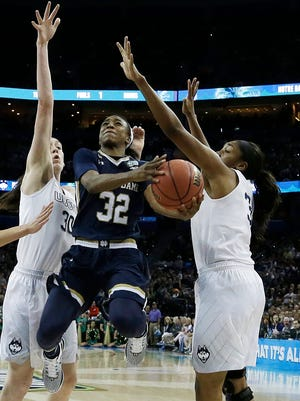 Notre Dame guard Jewell Loyd (32) heads to the hoop as Connecticut forward Breanna Stewart (30) and Connecticut forward Morgan Tuck (3) defend during the first half of the NCAA women's Final Four tournament college basketball championship game, Tuesday, April 7, 2015, in Tampa, Fla. (AP Photo/John Raoux)