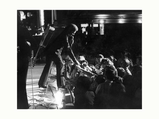 Johnny Cash steps over the footlights, extending welcoming