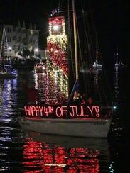 An illuminated boat floats down the Sheboygan River