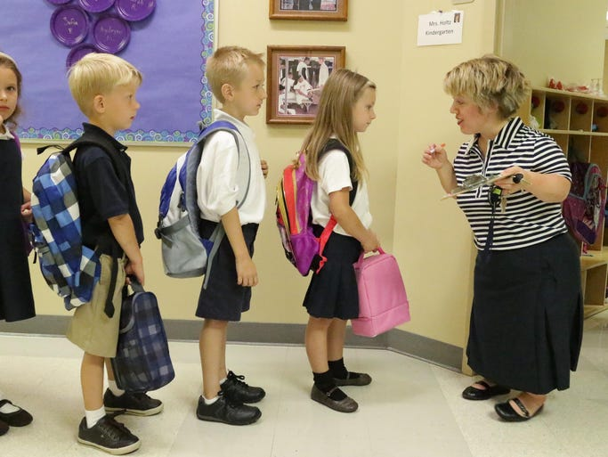 Lake Country Academy's direct instruction teacher Kristin Peterson, right, asks kindergarden students their milk choice for lunch during their first day of school Monday August 25, 2014 in Sheboygan.
