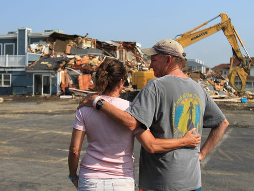 ASB 0722 McLoone's   Tim and Beth McLoone, react as their Iconic McLoone's Rum Runner Restaurant on Rt. 36 south in Sea Bright, is demolished after being destroyed during Superstorm Sandy, Monday, July 21, 2014. A new McLoone's Rum Runner is expected to reopen in the Spring of 2015. Photographer/Mary Frank