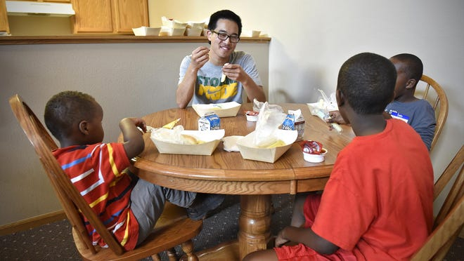 St. Cloud State University student Karl Johnson shares lunch Thursday as part of the YES Network program with children at a St. Cloud apartment building.