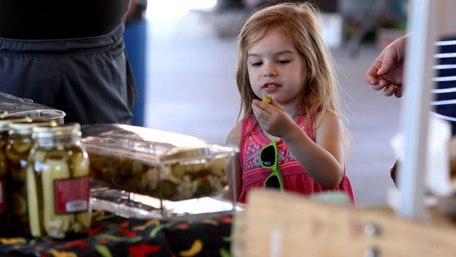 Elizabeth Foutz, 3, of Shelby Township looks at the pickle she just tasted from Safies during a farmers market at Detroit Eastern Market. Eastern Market hosts a farmers market on Tuesdays and Saturdays through the summer.
