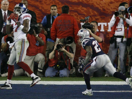 Plaxico Burress, left, scores a touchdown in the fourth