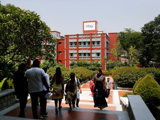 Infosys employees walk inside the company headquarters