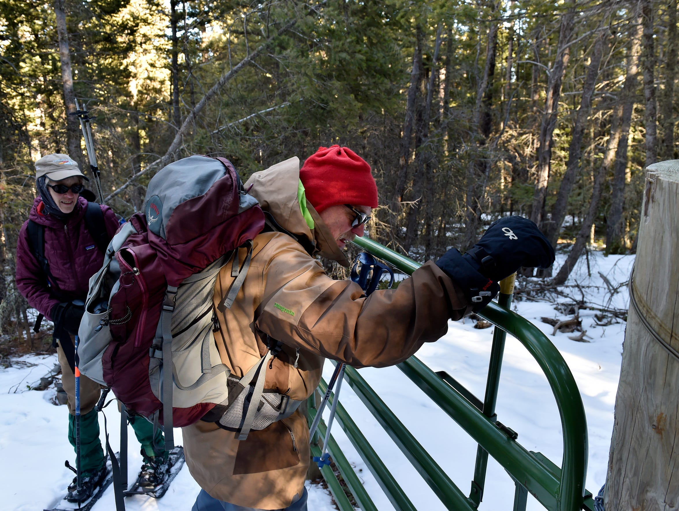 Mark Good, right, of the Great Falls-based Island Range Chapter of the Montana Wilderness Association, opens a gate while snowshoeing in the Big Snowy Mountains Wilderness Study Area near Lewistown.