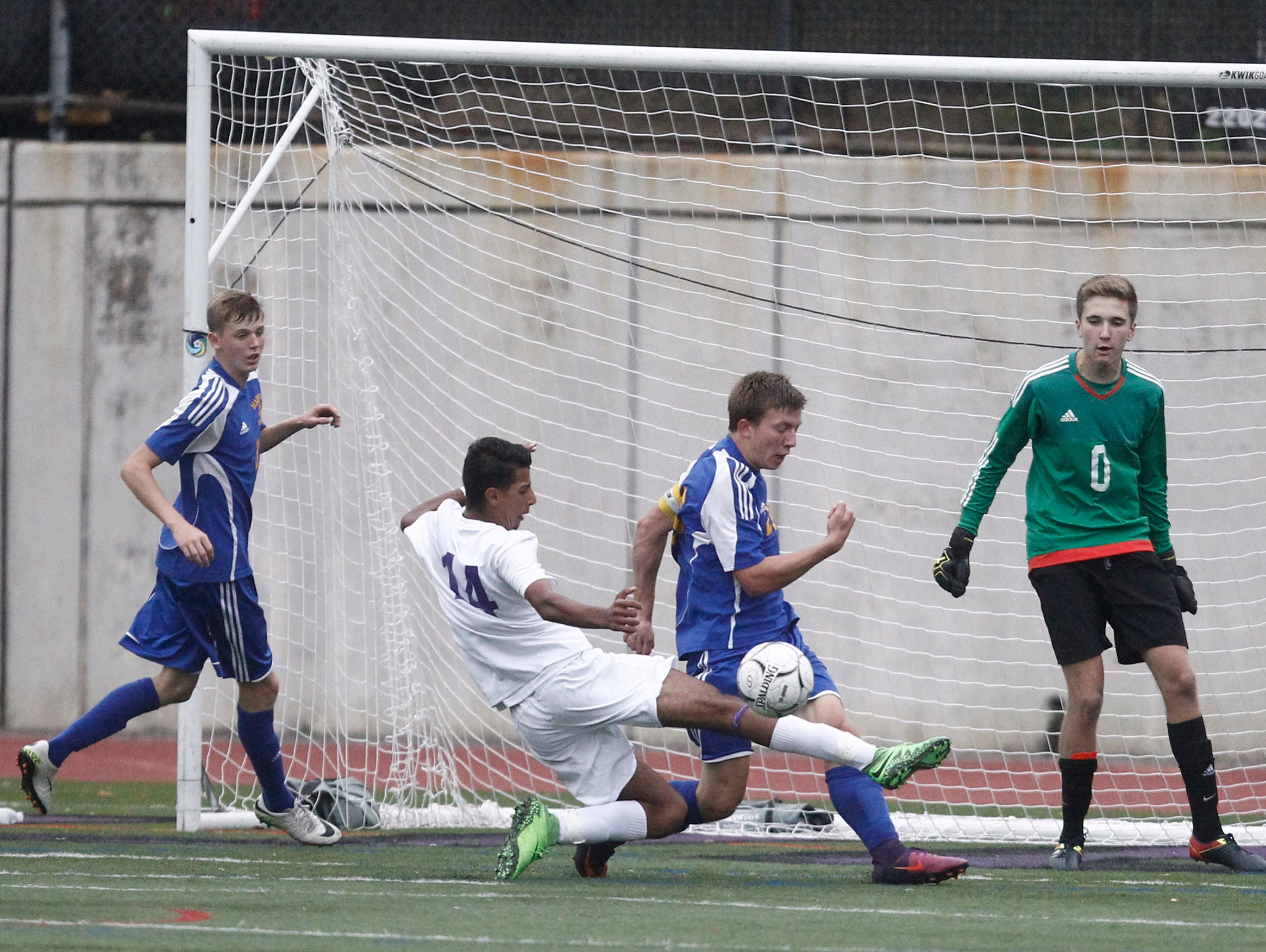 New Rochelle's Harwan Alzuabidi (14) slides for a shot on goal during their 2-0 win over Mahopac in the first round of the boys soccer Class AA playoffs at New Rochelle High School in New Rochelle on Thursday, October 20, 2016.