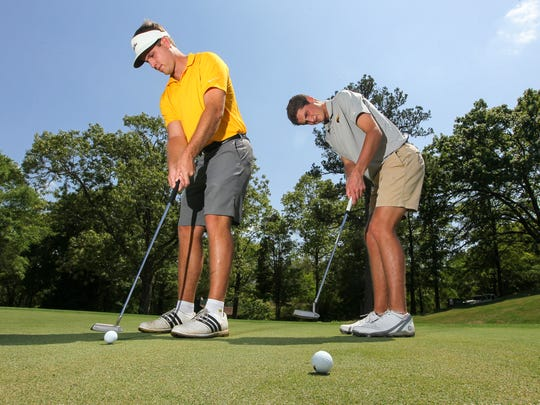 Grayson, right, and Weston Bell of the Anderson University golf team putt during practice at Cobbs Glen in Anderson on Thursday.