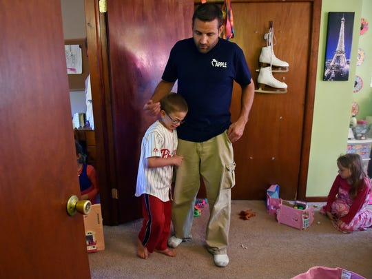 """Sean Kisielnicki, 7, is simultaneously comforted and escorted out by father Brian after Sean's sisters and cousins asked him to let them play by themselves after dinner Wednesday, June 7, 2017. """"Sean made me realize my kids aren't going to be here forever,"""" Brian says."""