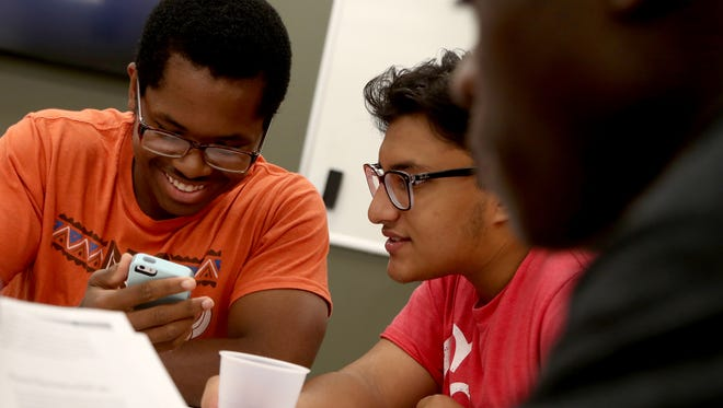 (L to R) Christofer Smith looks at pictures of animals that had gene modifications done to them with Kishwar Basith as Cedric Mutebi finishes reading stories about medical ethics in the Research Methods class taught by Dr. Farron McIntee on Friday, September 9, 2016 at WSU in Detroit. The three were selected for the Med-Direct program that gives free undergraduate tuition, room and board in addition to admittance and tuition into WSU medical school.