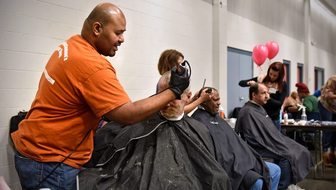 Volunteer Troy Johnson talks with a man while cutting his hair during the Project Connect event Wednesday, Oct. 19, at the River's Edge Convention Center in St. Cloud.