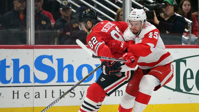 Blackhawks defenseman Jordan Oesterle and Red Wings center Dominic Turgeon fight for the puck during the second period at the United Center on Sunday.