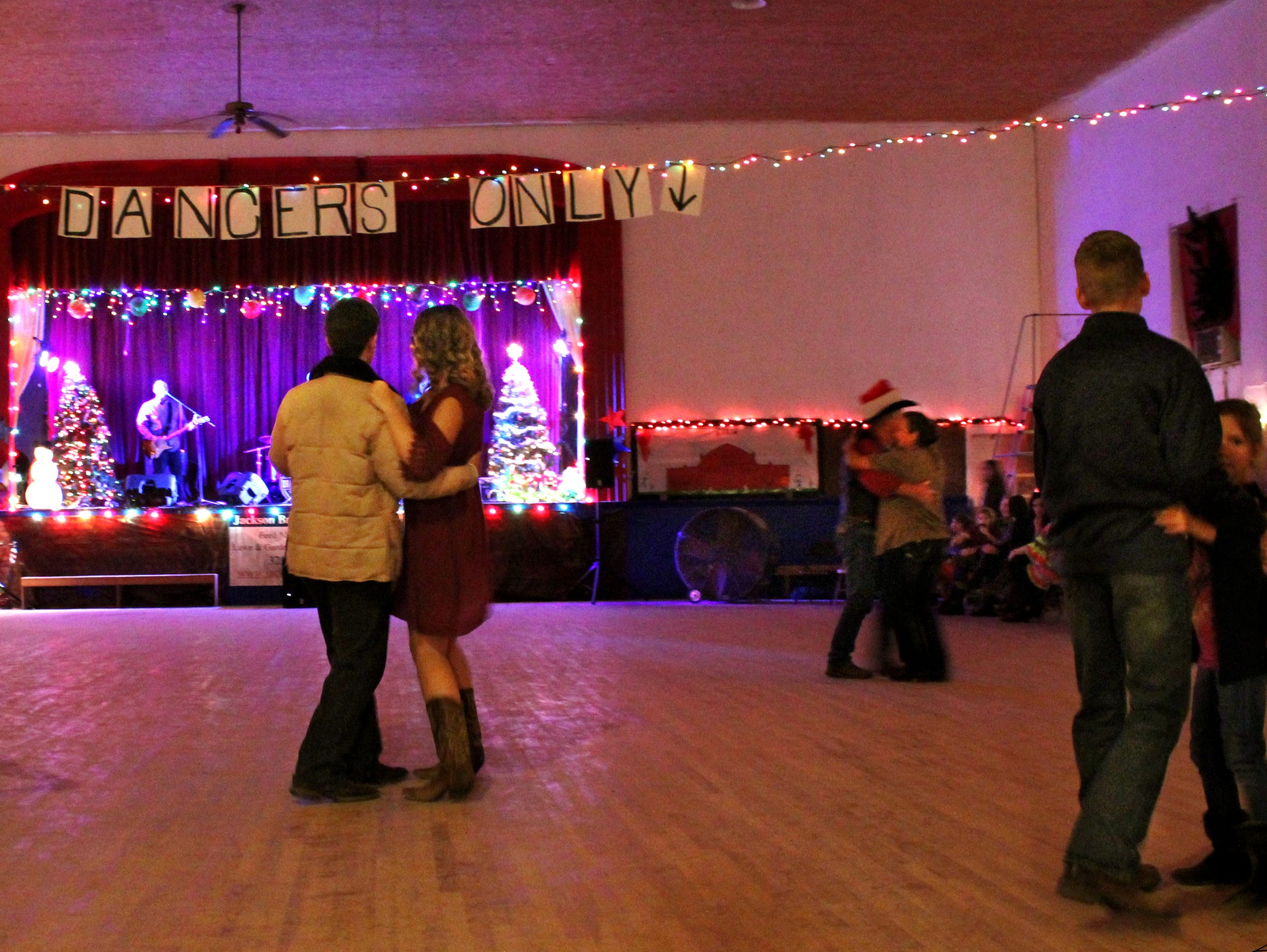 Couples become more silhouetted when the lights are dimmed at Oplin Dancehall. Lasts weekend, the Drake Hayes Band of Lubbock was the first band on stage in months at the dance hall. Other times, a deejay plays.