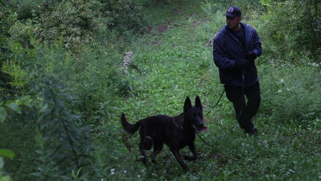 File photo: Southfield canine officer Jeff Medici and his dog Chase search for missing Troy resident Patrick Mikes Sr. in a rural and wooded area near Montrose, Mich., Thursday, August 9,  2012.
