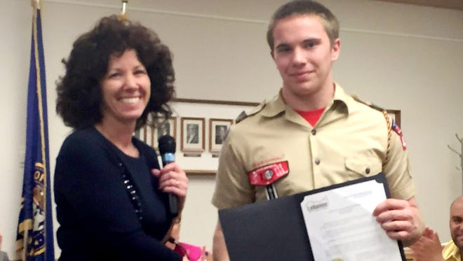 Lebanon Mayor Sherry Capello presents a certificate of recognition to Jacob Madderness, a member of Boy Scout Troop 412, who organized a community service project of about 20 volunteers who cleared brush from the lake trail path, and made and installed mile marker signs in Stoever's Dam Park.