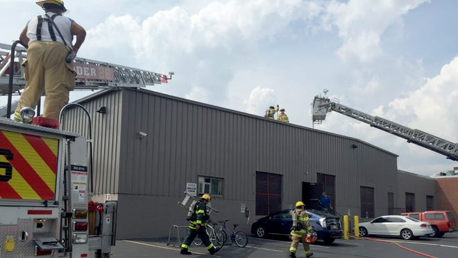 Firefighters carry a saw and ladder into Henry Molded Products, 71 N. 16th St., West Lebanon Township, where debris in a vent caught fire about 2:30 p.m. Thursday, July 28, 2016. The building was safely evacuated, and no injuries were reported.