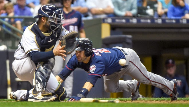 Twins second baseman Brian Dozier  scores after an error by Milwaukee Brewers second baseman Eric Sogard (not pictured) as  catcher Manny Pina waits for the ball in the seventh inning