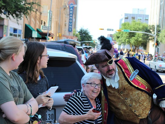 Linda Carleton, former dean of students at Hardin-Simmons University, lives out a dream by getting a hug (not a hook) from a swarthy pirate during Thursday's Storybook Parade. With her is her granddaughter, Katherine Strader, 13 (second from left), visiting Abilene from Tyler, and Strader's cousin Olivia Law, of Abilene.