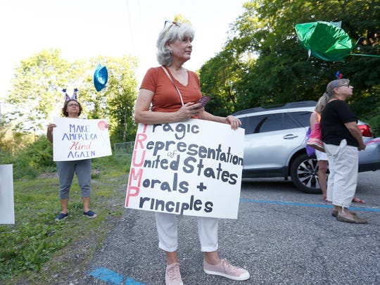 Stacy Trap holds a sign prior to demonstrators march through downtown Briarcliff Manor to protest the Trump organization's real property tax assessment challenge for the Trump National Golf Club in Briarcliff Manor on Wednesday, June 14, 2017.