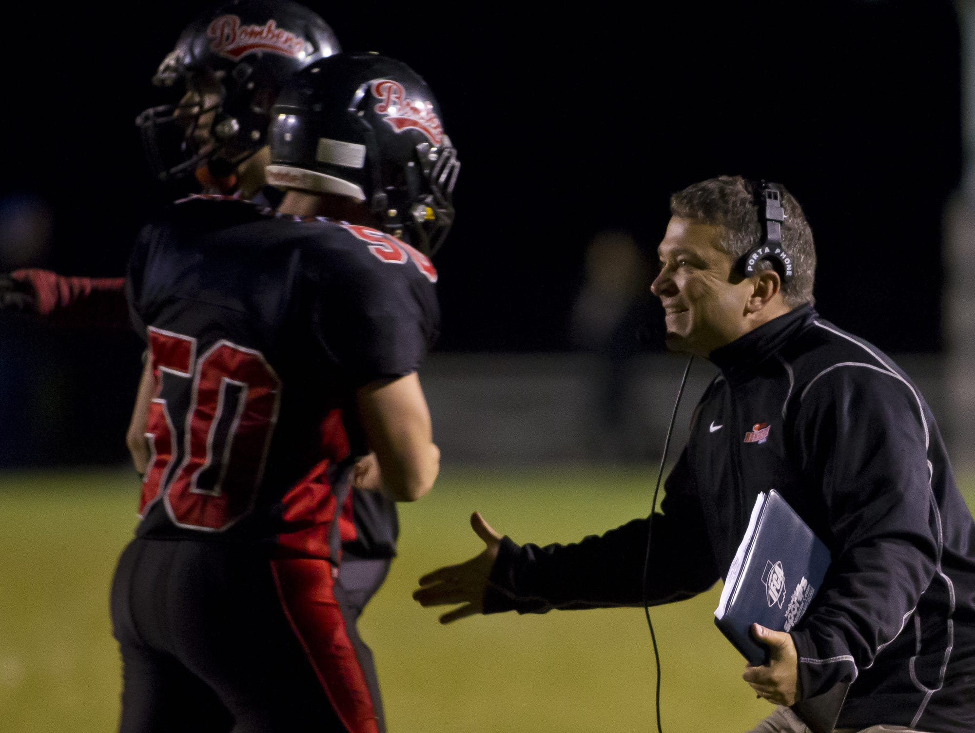 Rensselaer's coach Chris Meeks celebrates a stop during their game against Central Catholic Friday, October 10, 2014, in Rensselaer. The Bombers beat CC 9-0.